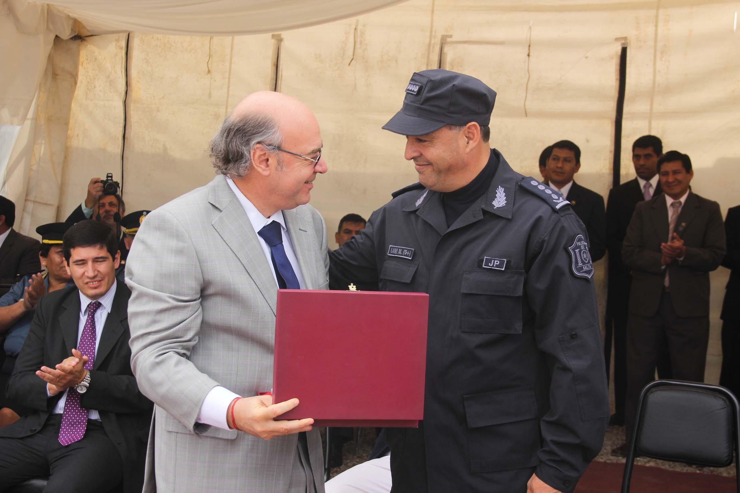 Abel Cornejo recibe del jefe de policía, Marcelo Lami una plaqueta.